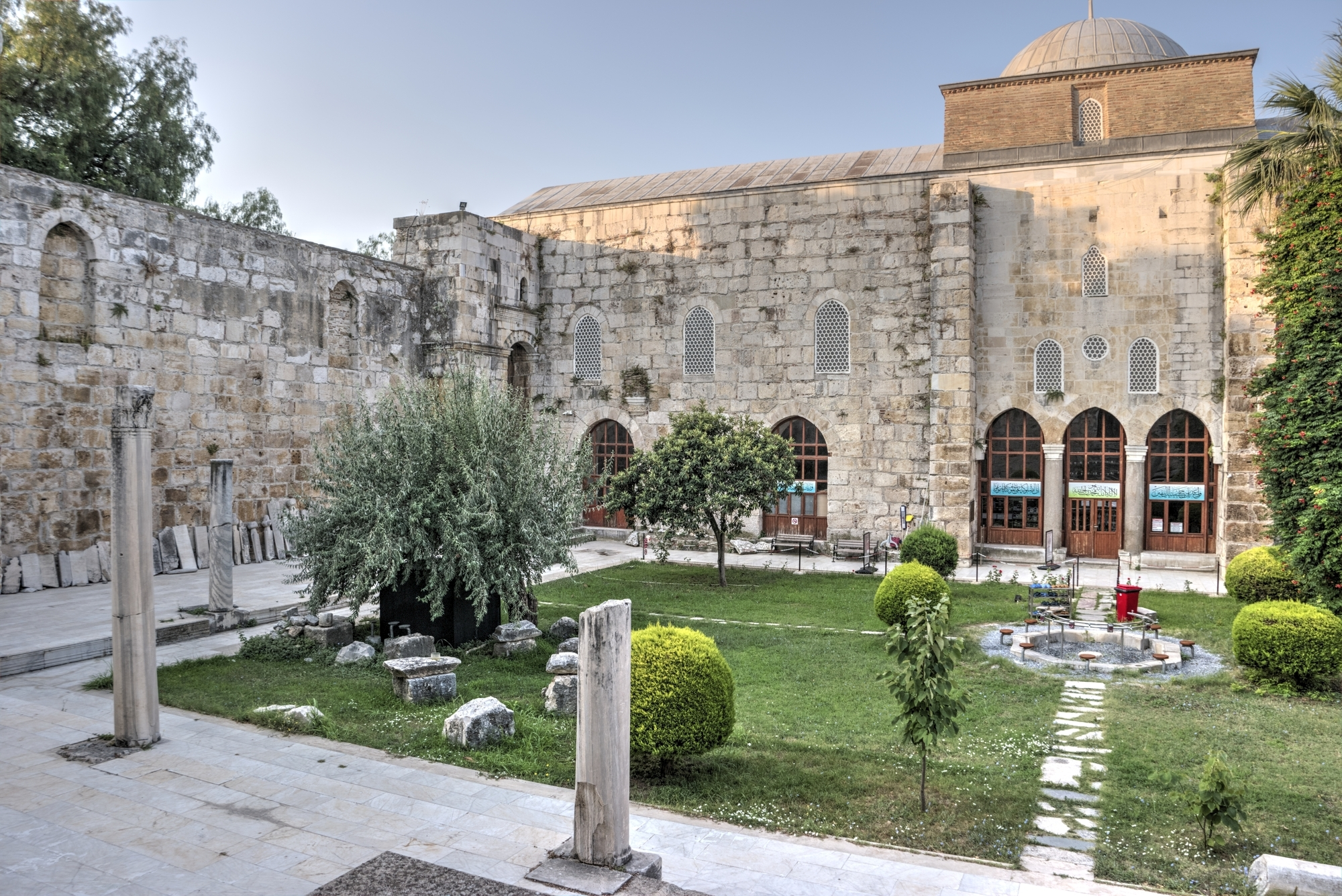 The courtyard of İsa Bey Mosque with columns and a fountain