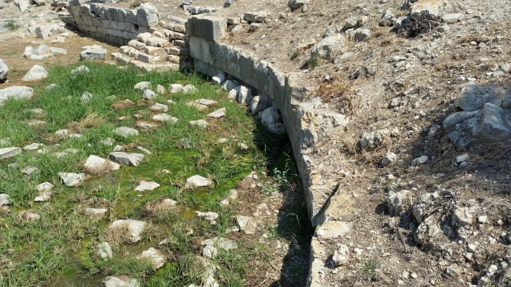 Archaic terrace wall threatened by the reopened water course
